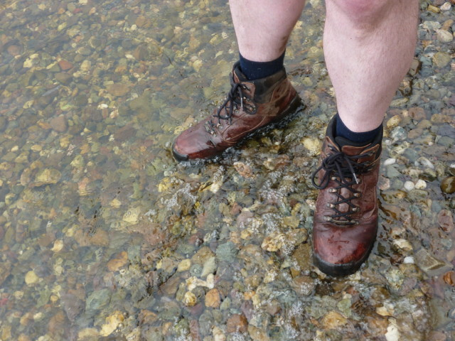 The author wearing a pair of hiking boots, stood in Loch Lomond