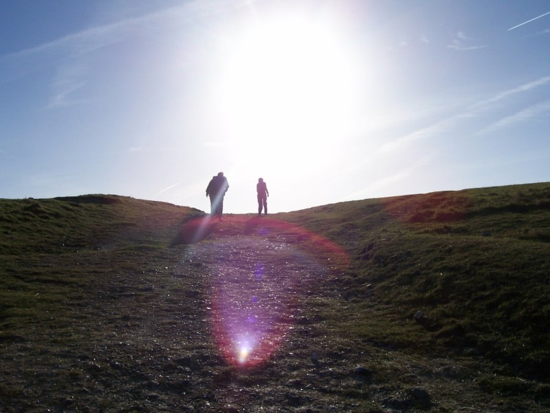 Walkers walk towards the sun on the South Downs Way