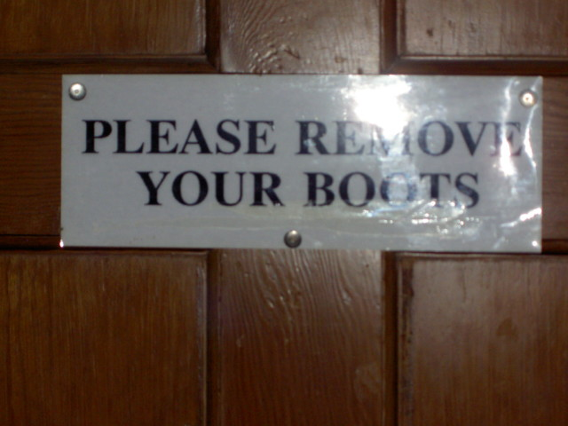 Sign saying 'Please remove your boots'