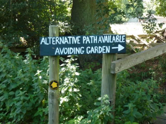 Sign saying alternative path available avoiding garden