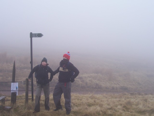 Two people stood next to a signpost, in the cloud
