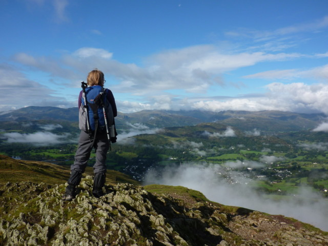 A walker stands at Wansfell Pike and admires the view