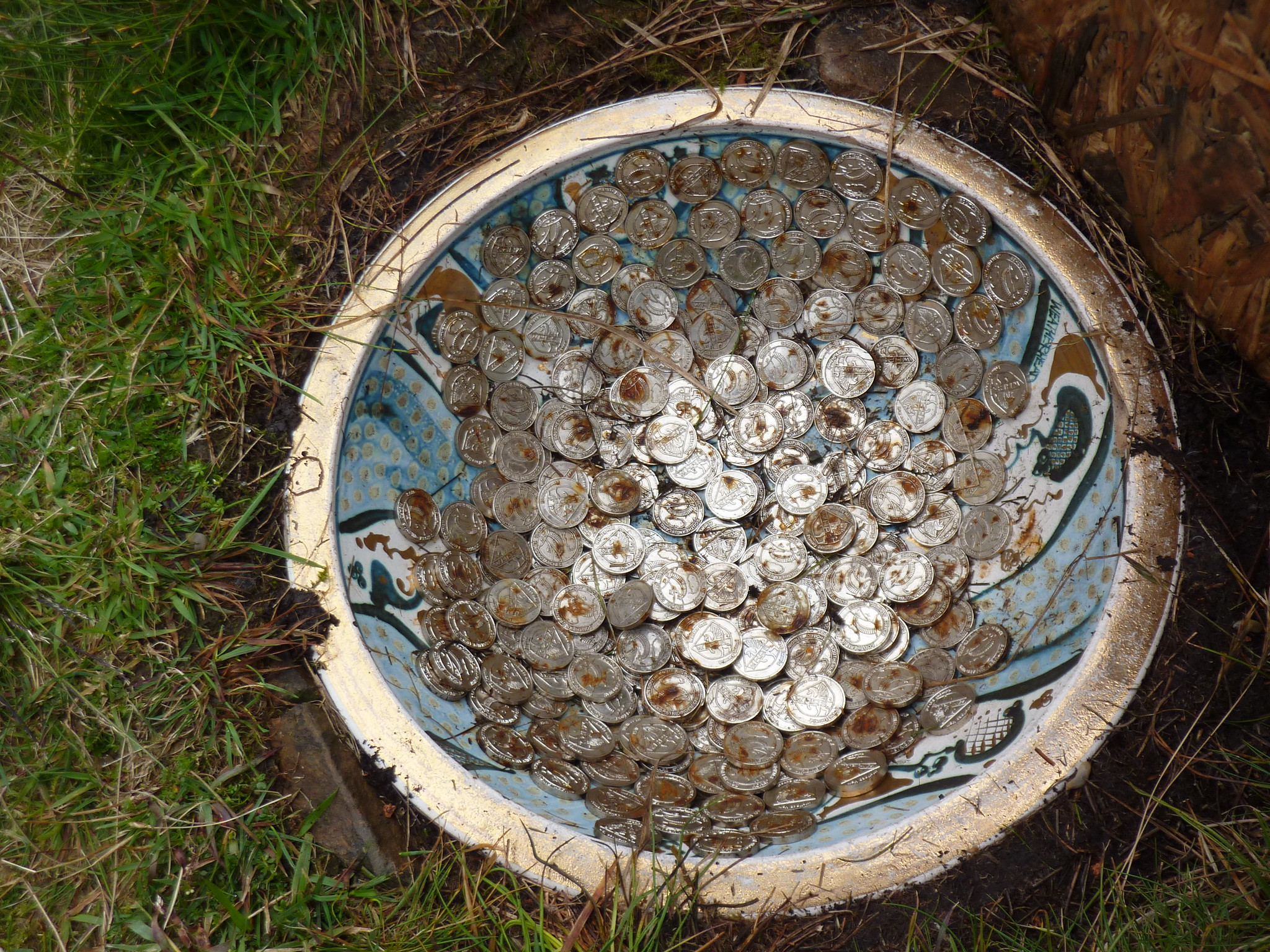 A nice pottery bowl full of rusting coins.