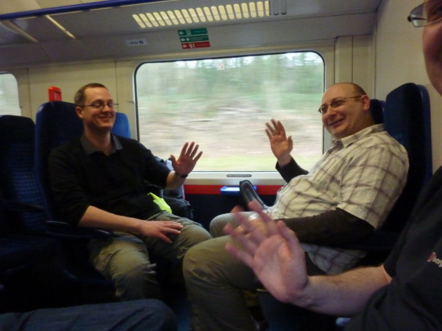 Simon and Mike wave on a train