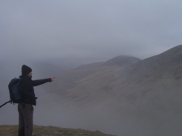A walker pointing at clouds in the Pentlands