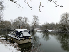 Snow covered boat moored on the River Thames near Cholsey