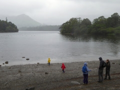 At the edge of Derwent Water in the rain with small cnildren