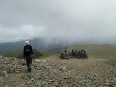 Catherine walking towards Helvellyn's summit shelter