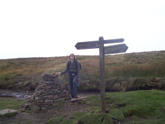 Catherine standing next to a sign post on Middle Bank Hill, on the Cam High Road part of the Pennine Way