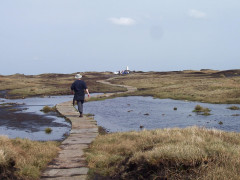 Walking on stone slabs over Black Hill, next to large peaty pools