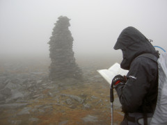 Checking the map next to a large cairn on Cross Fell