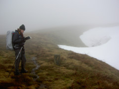 Catherine checks the map whilst stood next to snow on Green Fell