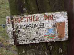 Faded sign advertising the Kirkstyle Inn to be the last pub till Greenhead