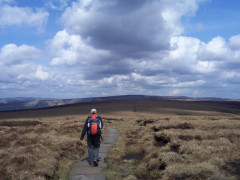 Walking on stone slabs on Mill Hill, on the Pennine Way