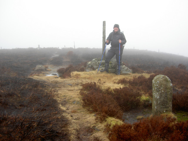 The author stood on the Pennine Way next to a wooden post.