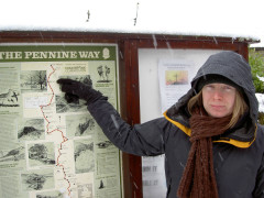 Pointing to the location of Byrness on a Pennine Way information board, as the snow comes down in Byrness