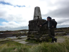 Standing next to the raised trig point at the summit of the Cheviot