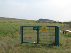 Gate leading onto the former Rainham landfill site, now full of grass