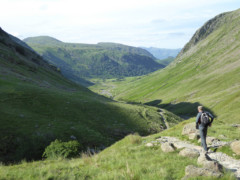 A walker strolls down a path in the Lake District