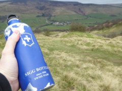 A blue Sigg bottle on a hillside