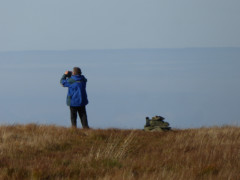 Man taking photos at the summit of Mungrisedale Common