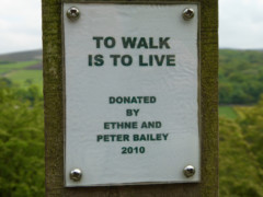 Plaque on a signpost saying 'To walk is to love""