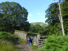 Two walkers next to gate at the beginning of the path up to St Sunday Crag