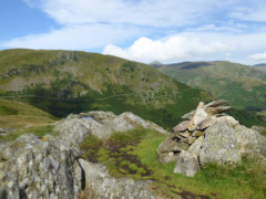 Arnison Crag's summit cairn, with Birks in the background