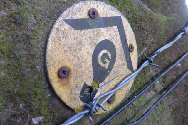 A Gritstone Trail waymark, protected by barbed wire
