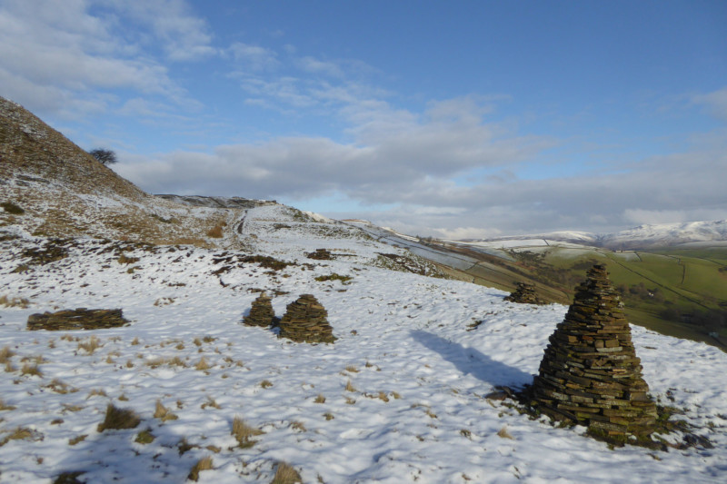 Cairns surrounded by snow on Cracken Edge