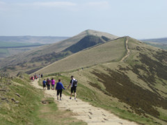 A steady stream of walkers walk along the Great Ridge to Hollins Cross