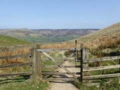 A gate with Peak District hills behind it