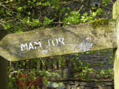 A weathered wooden signpost pointing to Mam Tor