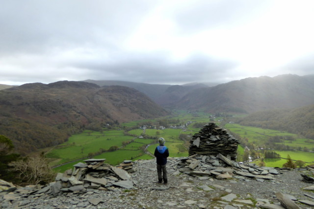 A child looks out across Borrowdale from the side of Castle Crag