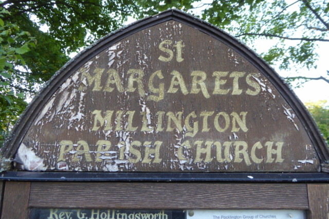 Faded and worn sign for St Margaret's Church in Millington