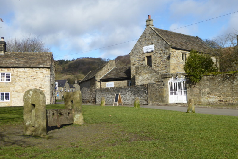 Eyam village green, with a set of stocks in the foreground