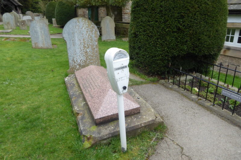 A parking meter next to a gravestone