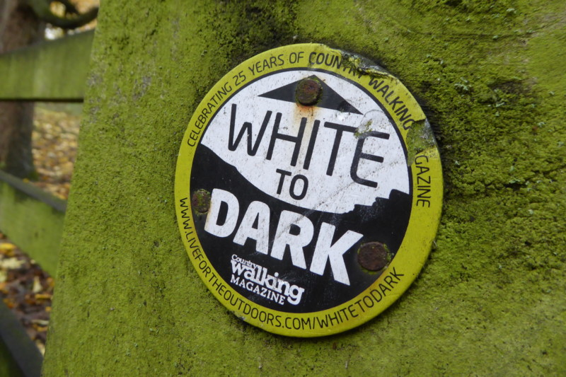 A rather battered White to Dark waymark sign near Bakewell
