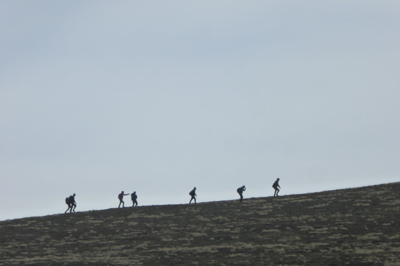 Silhouettes of walkers climbing up a hill