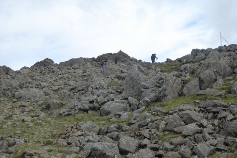 A walker scrabbles over the rocks to get to the top of High Stile